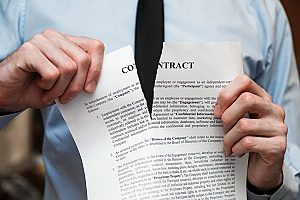 a company employee tearing up his paper contract after having performed a breach of employment contract by selling client information