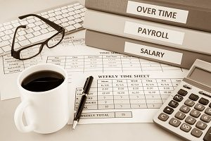 a dest with a time sheet on it and documents regarding employees overtime hours, salary, and requirnments under the Fair Labor Standards Act