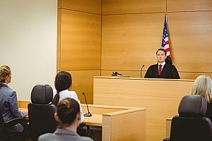 an employee in the courtroom with his employer and employment law attorney to prove that his employer breached his employee non compete agreement several times