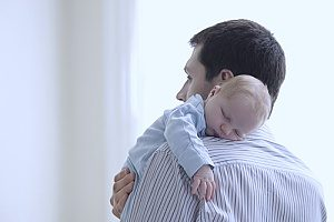 a man holding his newborn son after having spoken to an employment law attorney in case his employer did not allow him to exercise his FMLA rights
