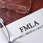 a stethoscope on top of a booklet containing the FMLA guidelines to represent which FMLA benefits requests employers must allow