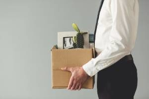 A man taking a box of his stuff home after wrongful termination