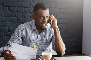 man angry on the phone because of wrongful termination