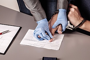 a man charged with a felony being fingerprinted by an officer